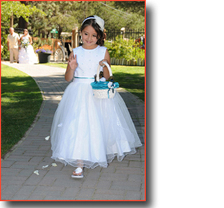 Flower girl walks the aisle dropping flower petals
