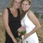 The bride with her maid of honor on the beach