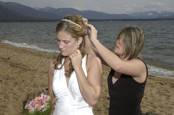 One of the bridesmaids helps the bride fix her hair