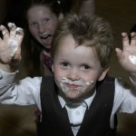 Ring bearer boy eats cake at reception