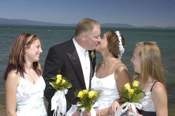 The bride and groom have their first kiss while their children watch