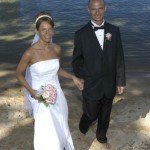 The happy couple smiles at the camera during their beach wedding at Sand Harbor