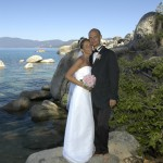 The married couple pose on a rock in Lake Tahoe