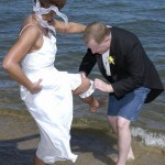 The groom removes the garter from the bride on the beach