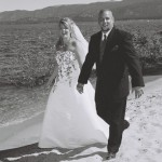 Newlyweds walk hand in hand along the beach