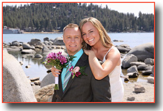 Newlyweds hug by the rocks at the cove
