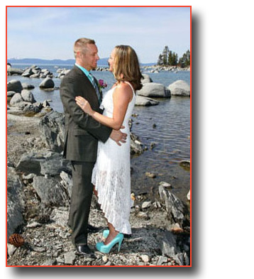 Bride and groom pose by the rocks at the shoreline